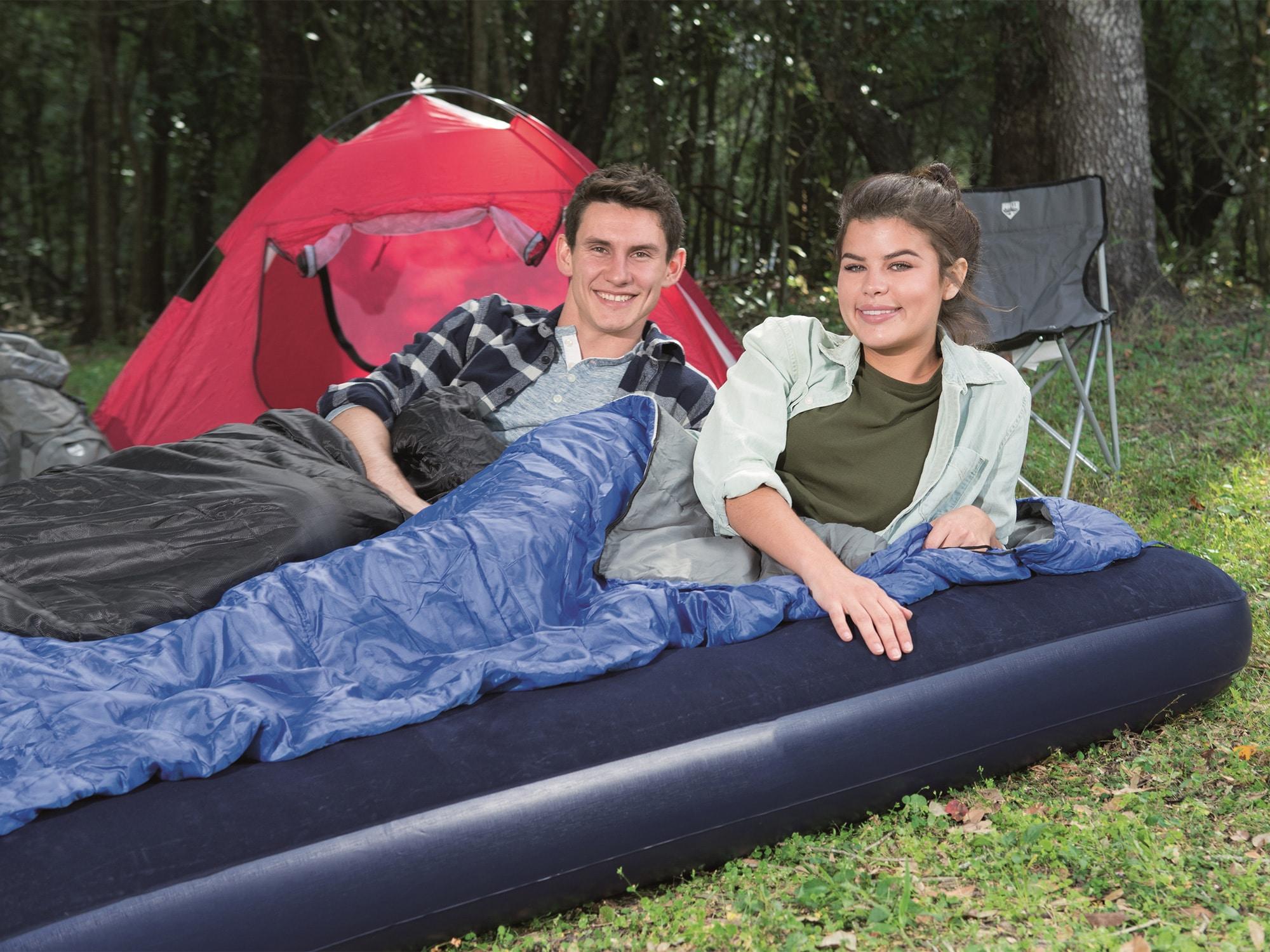 To personer liggende i sovepose på oppblåsbar madrass